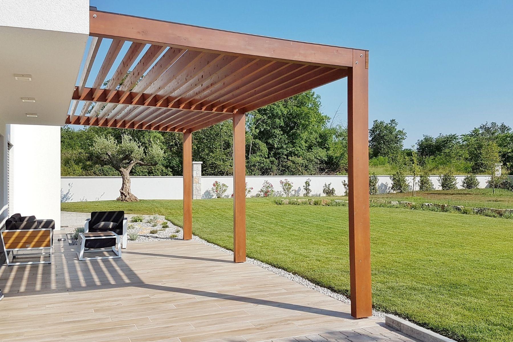 Pergola bioclimatique fait la transition entre la maison et le jardin.