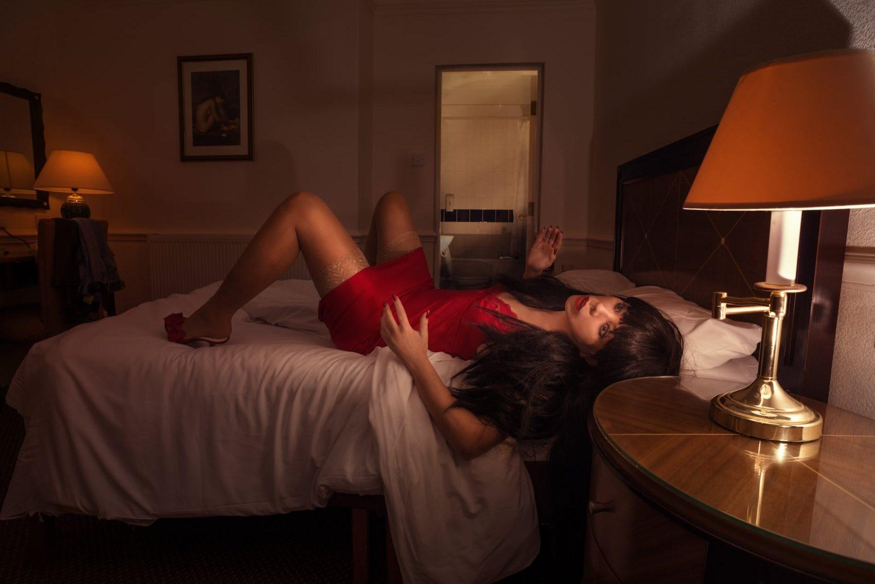 Poupée adulte posée sur un lit.