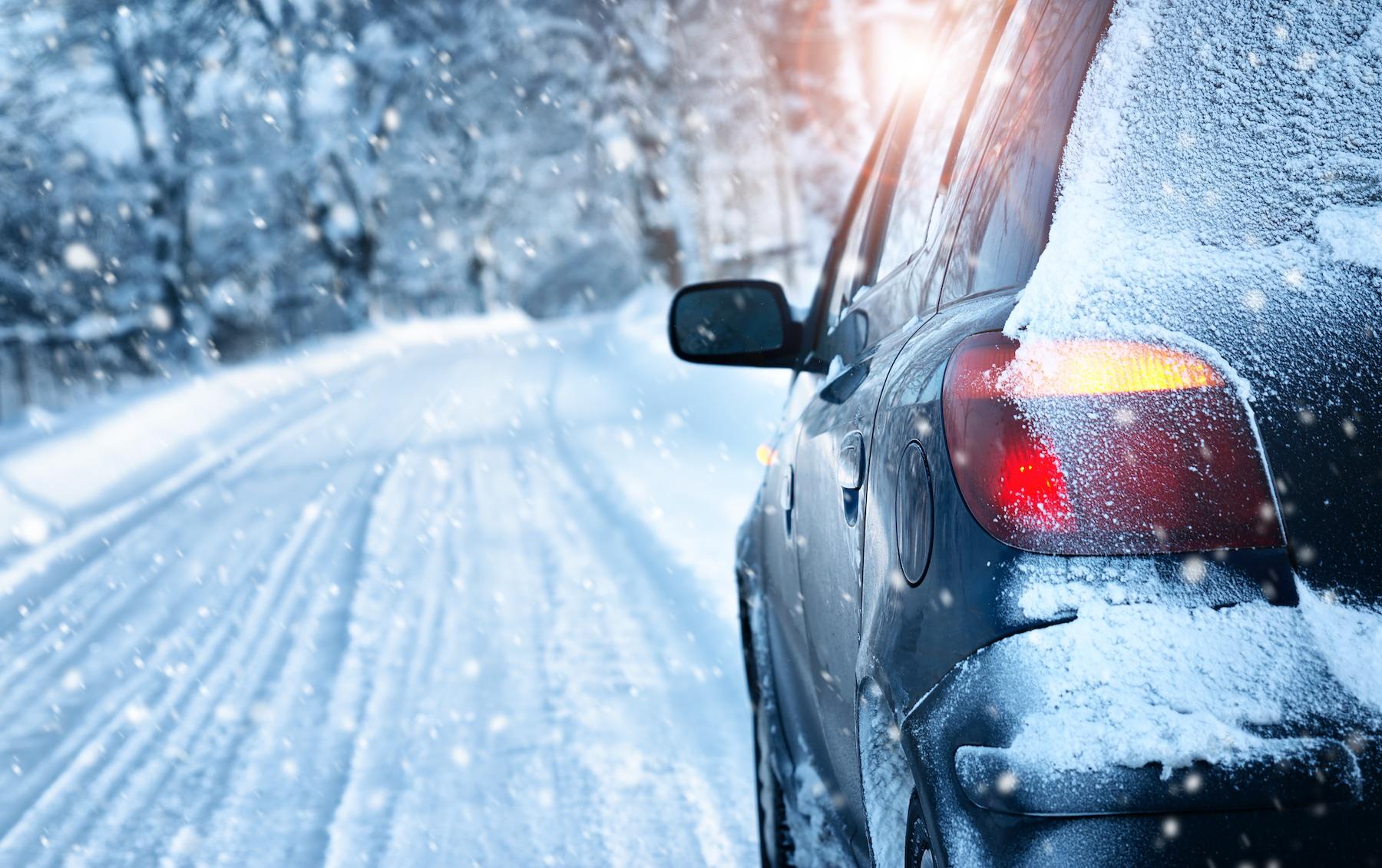 Voiture roulant sur une route enneigée