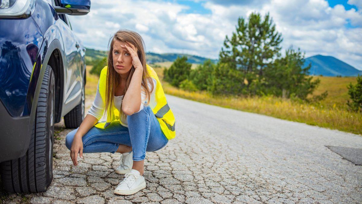 Jeune femme dépitée face à une roue crevée