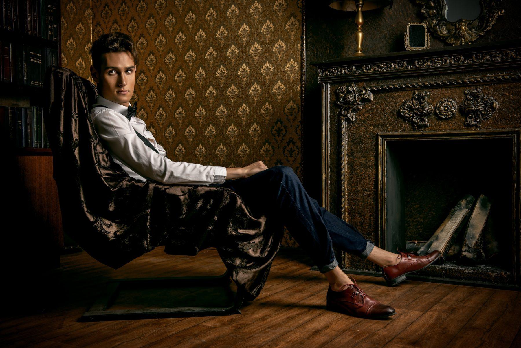 Homme au style dandy assis dans un fauteuil de cuir face à une cheminée.