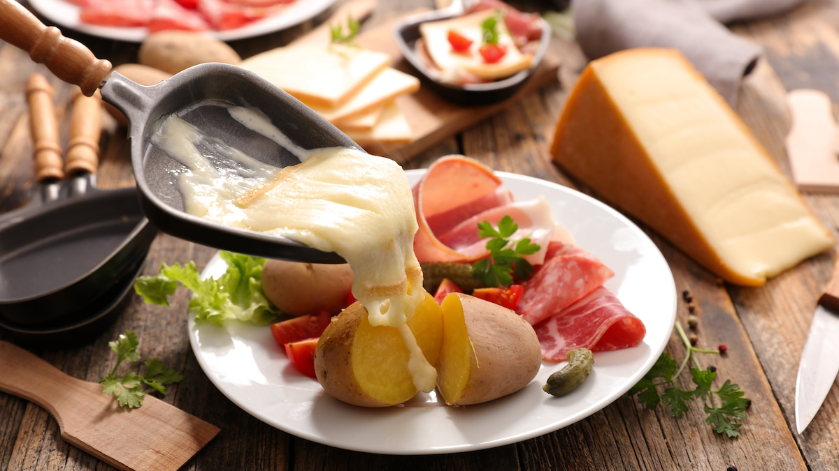 Tous les ingrédients d'une bonne raclette : fromage fondu, pommes de terre, charcuterie et condiments