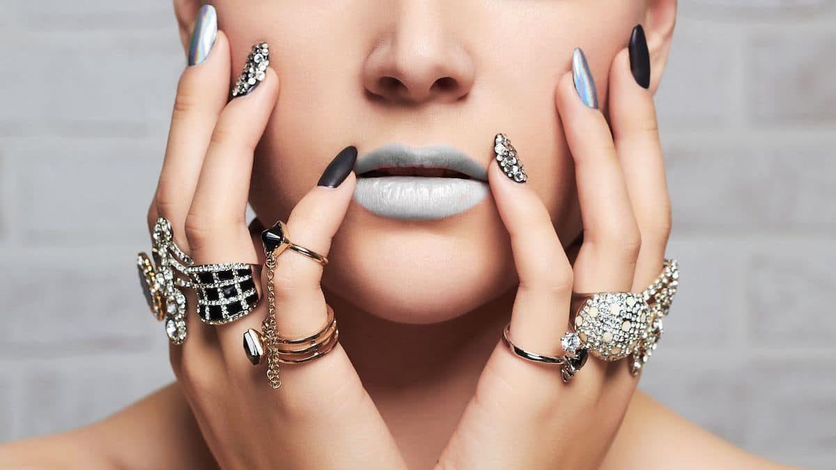 Jeune femme avec des bagues en diamant sur les doigts de ses deux mains.