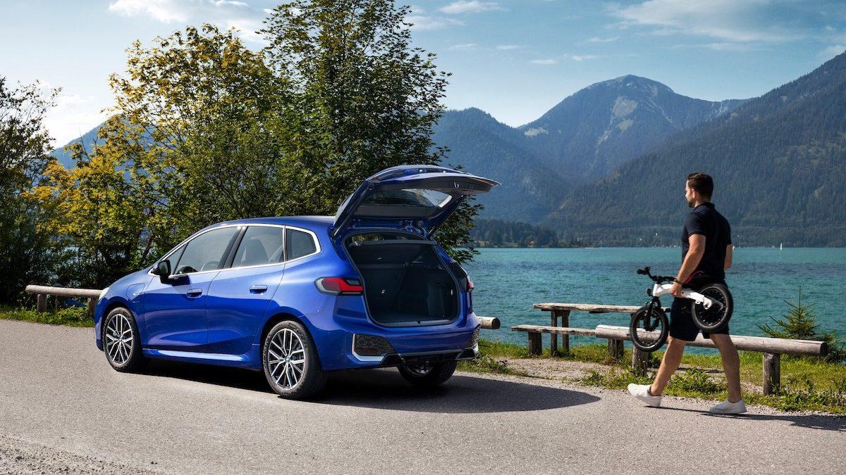 BMW série 2 coffre ouvert au bord d'un lac de montagne.